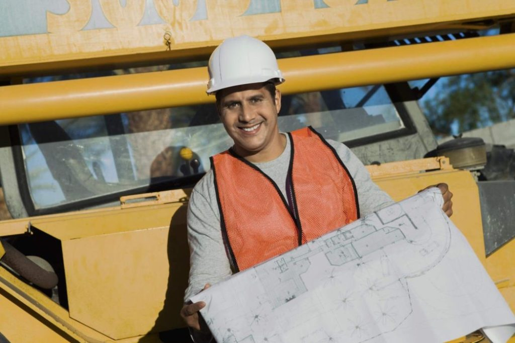Foreman holding a blueprint to see where to poor concrete