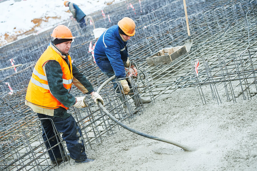 Two workers wearing protective clothing pooring and evening out concrete amongst rebar structures