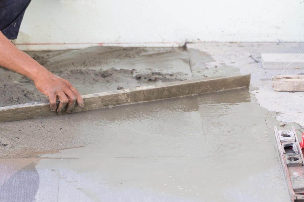 Worker smoothing out a repaired concrete surface