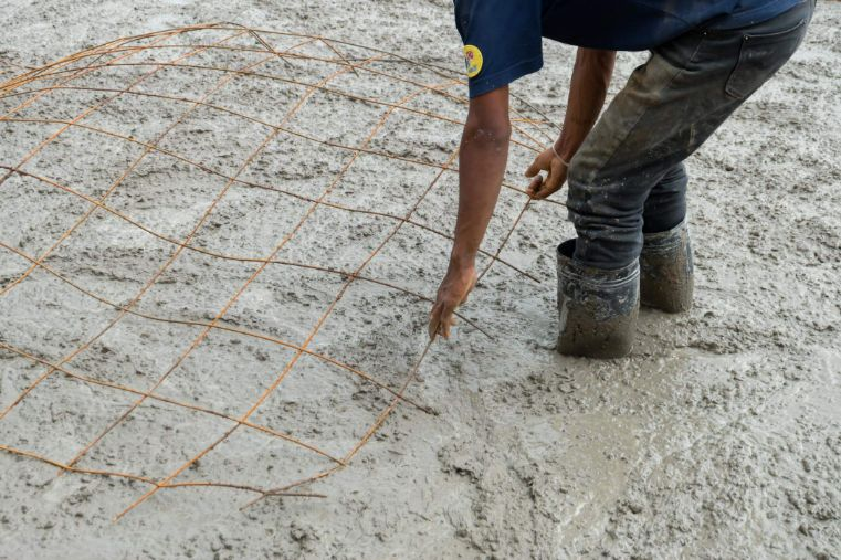 Worker applying rebar whilst standing in freshly poored concrete