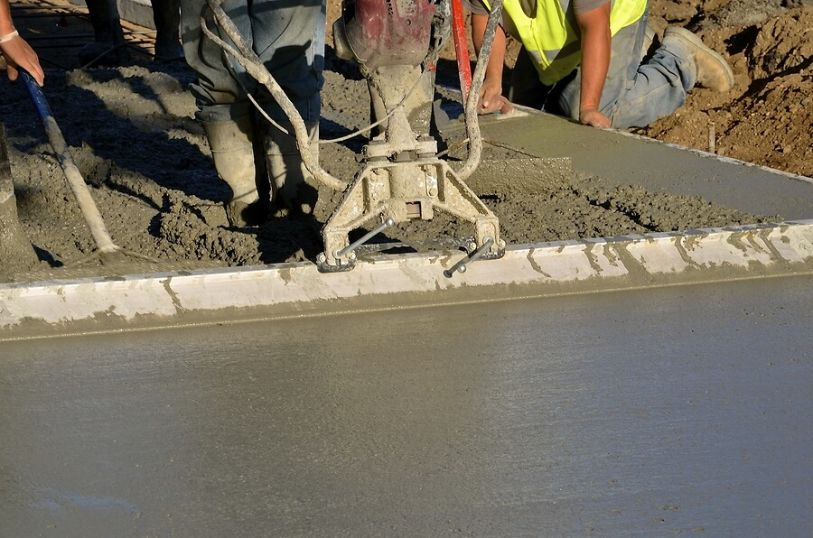 Two workers screening concrete on a sidewalk in front of a residential project