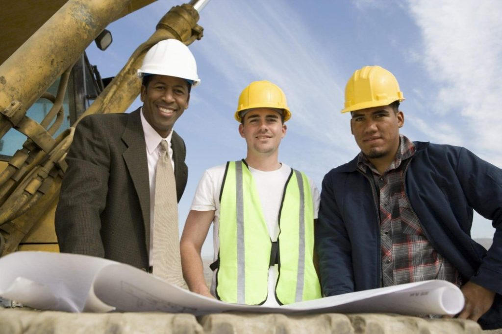 Engineer, foreman and worker discussing a concrete pooring project