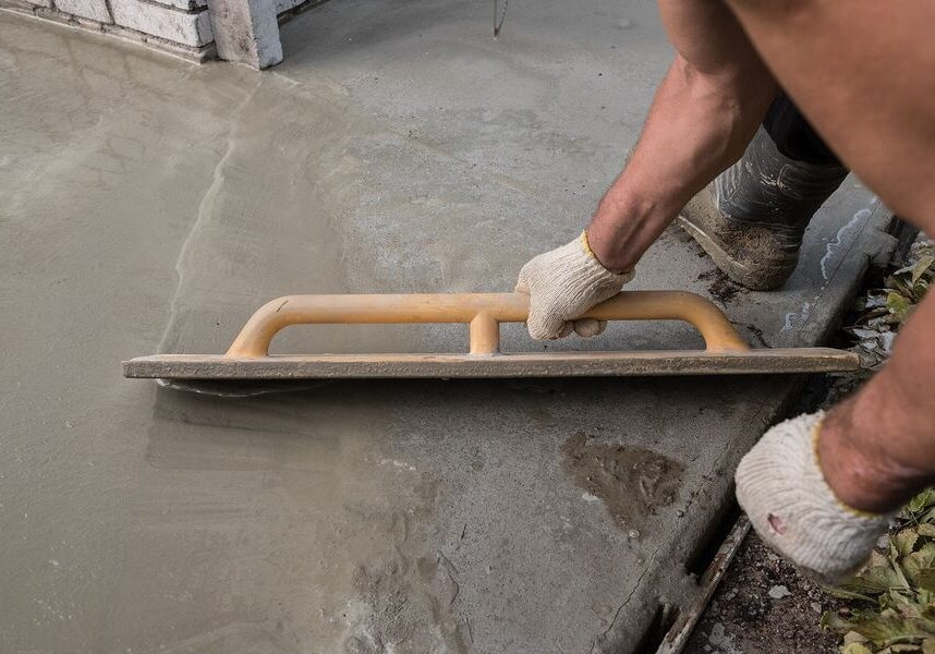 Worker smoothing out a concrete surface during a repair