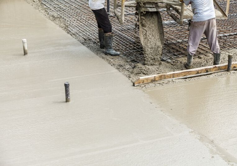 Builders pooring concrete during an industrial concrete project