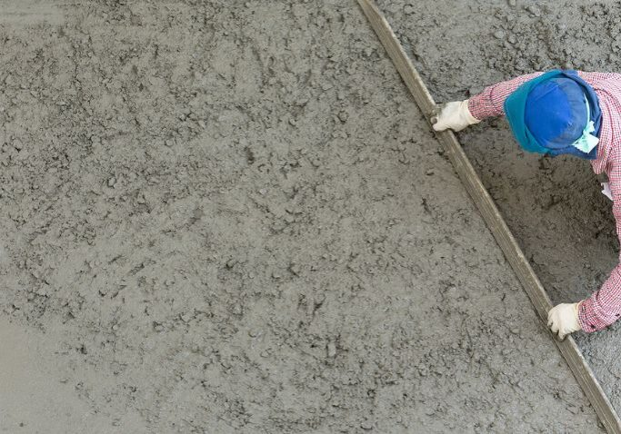Worker initiating the smoothing of a rough concrete surface