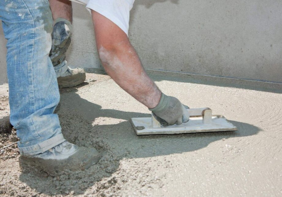 Worker finishing up a concrete surface with a small smoothing tool
