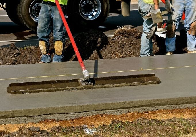 Concrete workers smoothing out a concrete molded surface